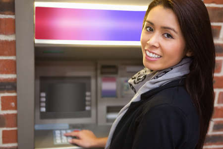 withdrawing: Woman withdrawing cash at an ATM