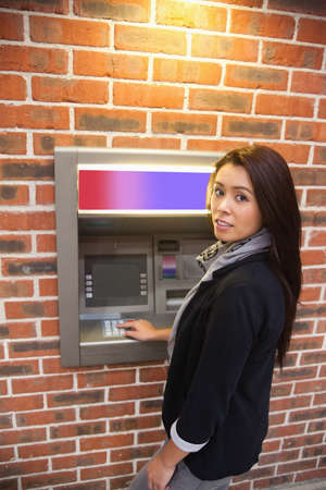 Portrait of a woman withdrawing cash at an ATM photo