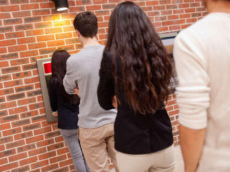People queuing to withdraw cash at an ATM photo