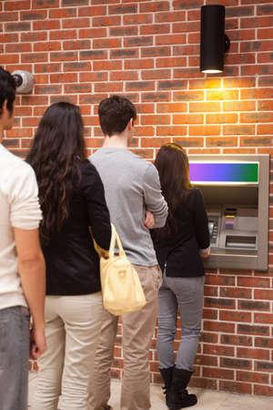 file d attente: Portrait de gens faire la queue pour retirer de l'argent � un guichet automatique