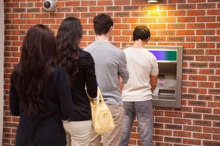 Junge Leute Schlange, um Bargeld in einem Geldautomaten abheben Lizenzfreie Bilder