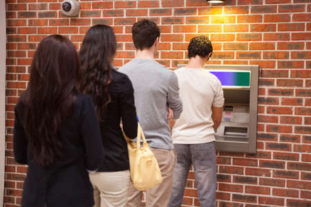 bank withdrawal: Young people queuing to withdraw cash in an ATM