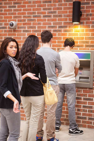 bank withdrawal: Portrait of an impatient woman queuing at an ATM