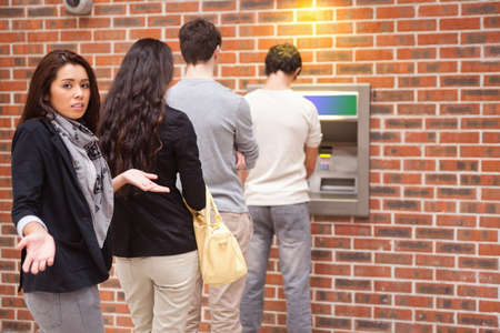 bank withdrawal: Impatient woman queuing at an ATM