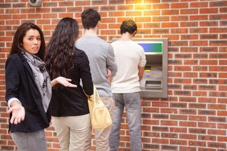 Impatient woman queuing at an ATM photo