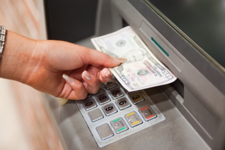 cash in hand: Retirar la mano femenina de d�lares en un cajero autom�tico Foto de archivo