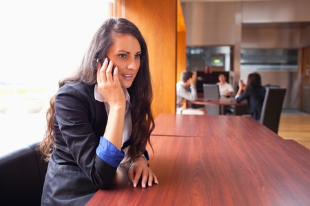 Young woman making a phone call while her coworkers are in a meeting photo