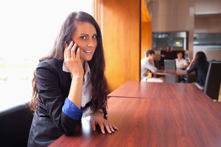 Smiling young woman making a phone call while her coworkers are in a meeting photo