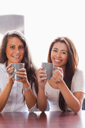 Portrait of friends having a cup of coffee while smiling at the camera photo