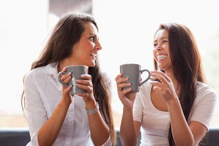 Laughing friends having a coffee in a cafe Stock Photo - 11187661