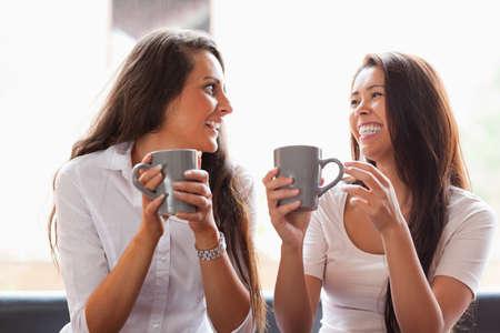 mujer tomando cafe: Riendo amigos que tienen un café en una cafetería