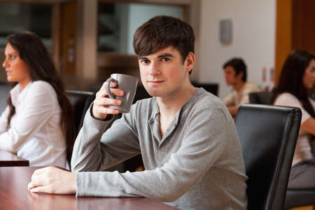 Young man having a coffee while looking at the camera photo