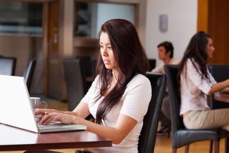 Young woman using a notebook in a cafe photo