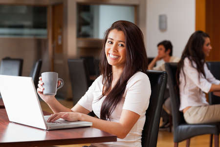 Cute woman using a laptop in a cafe photo