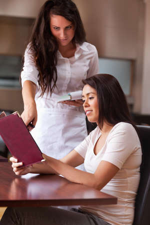 Portrait of a young waitress advising a customer pointing something on the menu photo