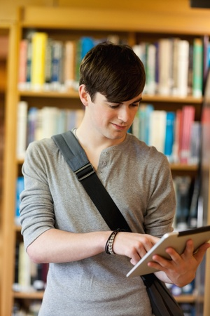 Portrait of a young student using a tablet computer in the library photo