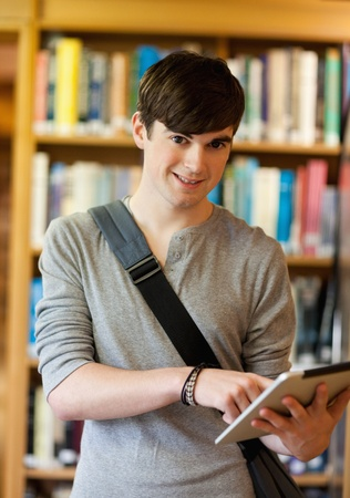 Portrait of a smiling student using a tablet computer in a library photo