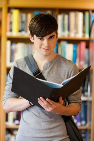 Portrait of a smiling student holding a binder while looking at the camera Stock Photo - 11184790
