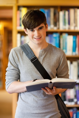 Portrait of a handsome student holding a book in the library Stock Photo - 11184774