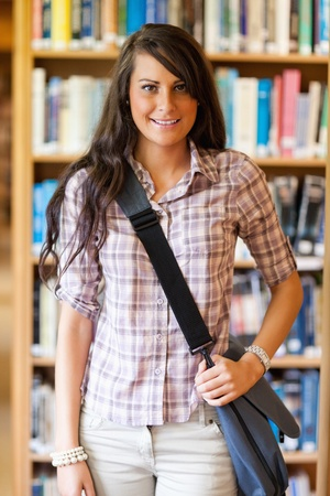 successful student: Portrait of a student holding her bag in a library