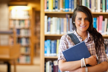 Portrait of a student posing with a book in the library photo
