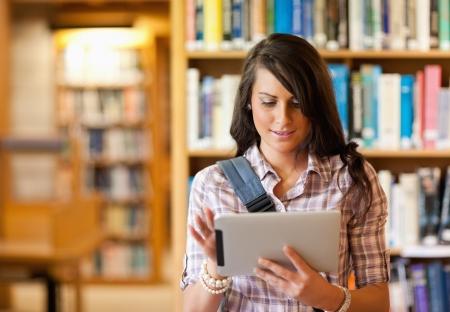 biblioteca: Estudiante joven linda con un equipo Tablet PC en una biblioteca