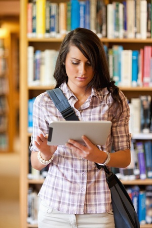 Portrait of a gorgeous student using a tablet computer in a library photo