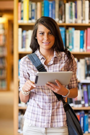 Portrait of a smiling young student using a tablet computer in a library photo