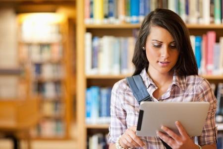 biblioteca: Joven estudiante se centr� con un equipo Tablet PC en una biblioteca