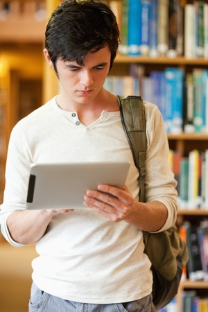 Portrait of a serious student using a tablet computer in a library photo