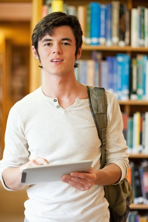 Portrait of a serious student holding a tablet computer in a library photo