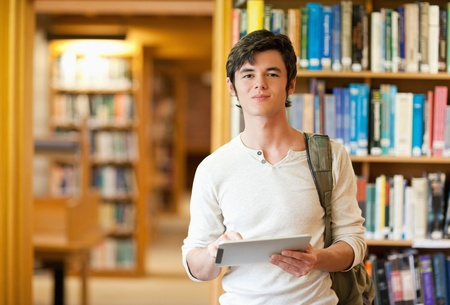 Serious student holding a tablet computer in a library photo