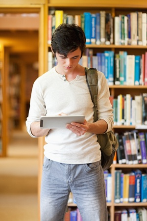 Portrait of a focused student using a tablet computer in a library photo