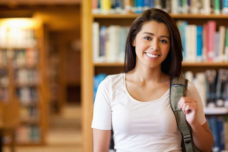 college campus: Gorgeous student standing up in a library Stock Photo