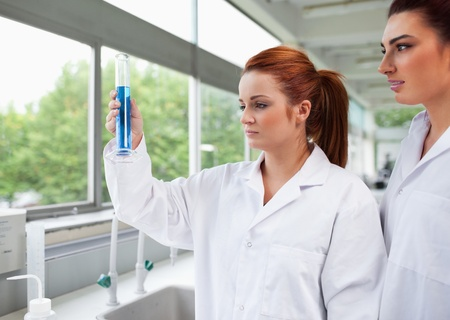 Science students looking at a graduated cylinder in a laboratory photo