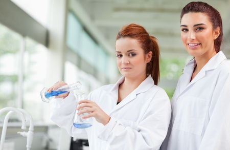 biochemist: Scientists pouring blue liquid in an Erlenmeyer flask in a laboratory Stock Photo