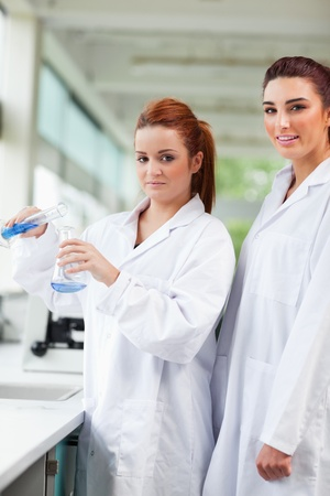 Portrait of scientists pouring blue liquid in an Erlenmeyer flask in a laboratory photo