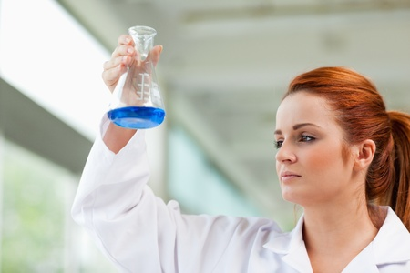Scientist looking at a blue liquid in an Erlenmeyer flask photo
