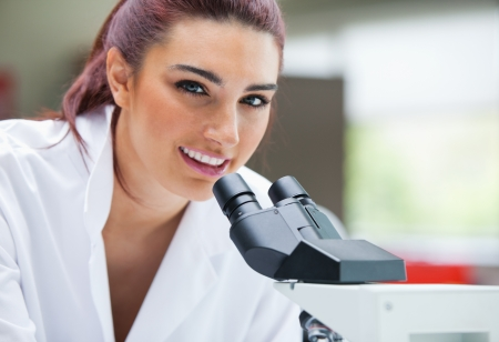 Close up of a scientist posing with a microscope in a laboratory photo