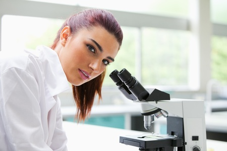 experimentation: Brunette posing with a microscope while looking at the camera Stock Photo