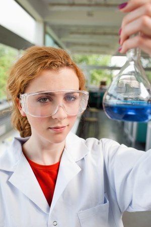 compound eyes: Portrait of a science student holding a flask with protective glasses