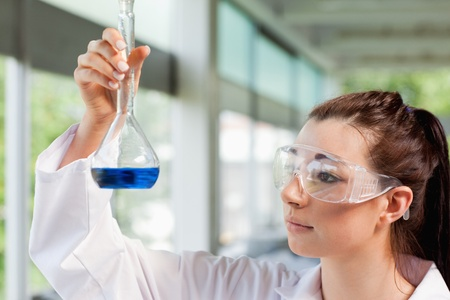 compound eyes: Young science student looking at a blue liquid in a laboratory Stock Photo