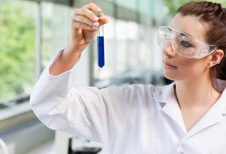 Science student looking at a test tube in a laboratory photo