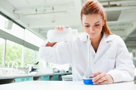 biochemist: Red-haired focused scientist pouring liquid in a flask in a laboratory