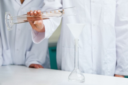 Female hands pouring liquid in a laboratory photo