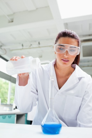 Portrait of a female science student pouring liquid in a laboratory photo