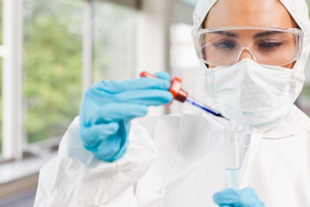 Protected science student dropping a liquid in a test tube in a laboratory Stock Photo - 11212484