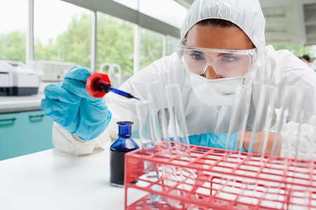 Protected cute female scientist dropping blue liquid in a test tube in a laboratory photo