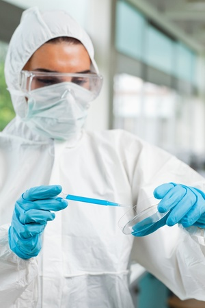 Portrait of a protected female science student dropping blue liquid in a Petri dish in a laboratory photo