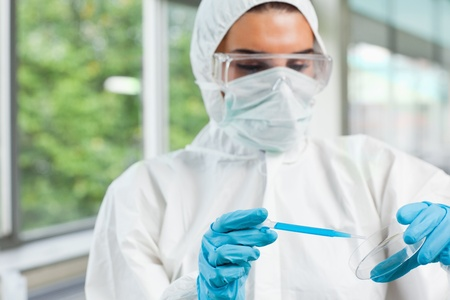 Protected female science student dropping blue liquid in a Petri dish in a laboratory photo